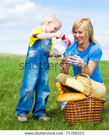 happy young  woman and her son having a picnic outdoor on a summer day (focus on the woman) - stock photo