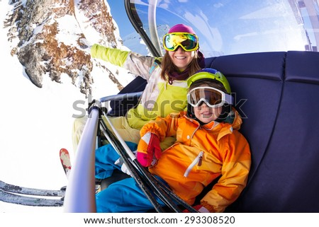 Happy young woman and little 4 years old boy sitting on the chair on ski lift smiling and wearing ski masks with mountain on background  - stock photo