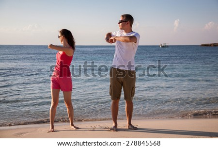 Happy young woman and man doing exercises on the sea coast at dawn - stock photo