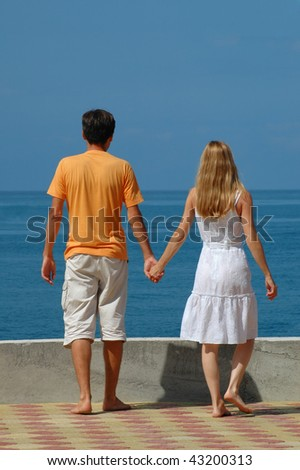 Happy young woman and man on the beach - stock photo