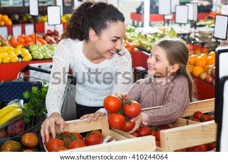 Happy young woman and small girl buying red tomatoes in supermarket
