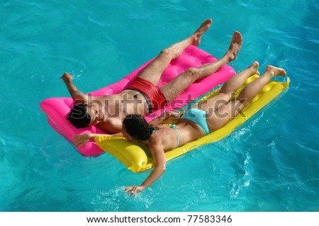 stock photo happy young woman and the man floating on a mattress in water pool 77583346