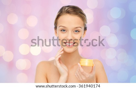 happy young woman applying cream to her face - stock photo