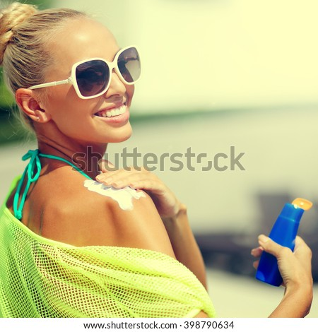 Happy young woman applying sunscreen lotion