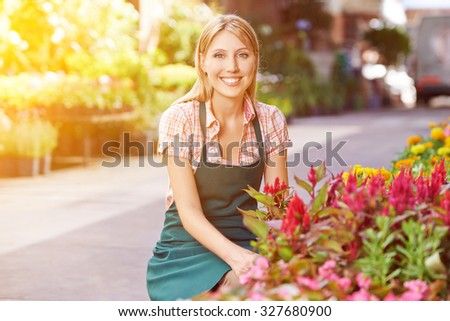 Happy young woman as gardener in front of a flower shop - stock photo