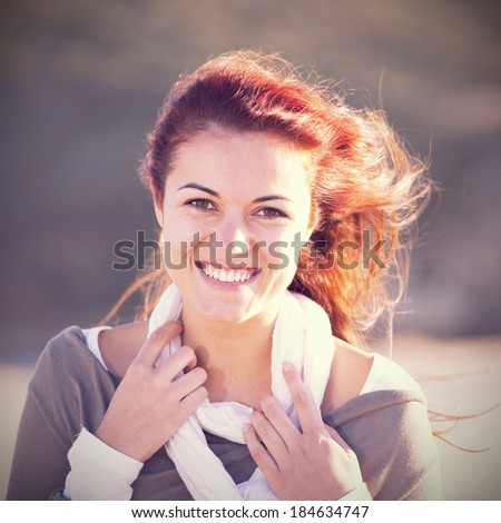 Happy young woman at the beach enjoying the sunny day