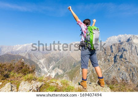 Happy Young Woman at Top of the Mountain - stock photo