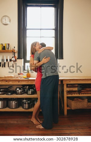 Happy young woman being hugged by her boyfriend in the kitchen. Cheerful young couple embracing each other in morning at home. - stock photo