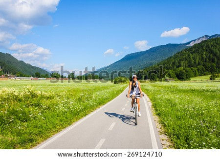 Happy young woman biking at countryside with beautiful scenery of mountains and field. - stock photo