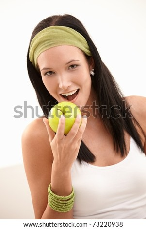Happy young woman biting green apple, smiling, isolated on white.?