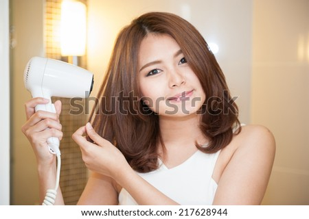 Happy young woman blow drying hair