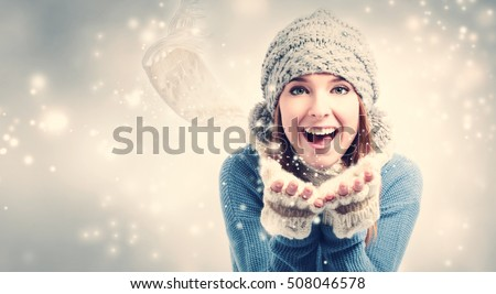 Happy young woman blowing snow in snowy day