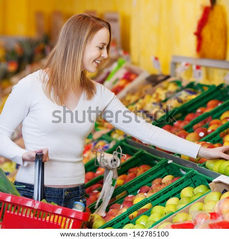 Happy young woman buying apples in grocery store - stock photo