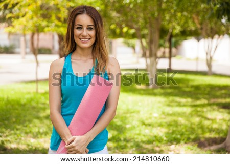 Happy young woman carrying a yoga mat for her practice at the park