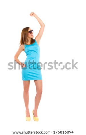 Happy young woman celebrating success. Smiling beautiful woman with raised hand. Full length studio shot isolated on white. - stock photo