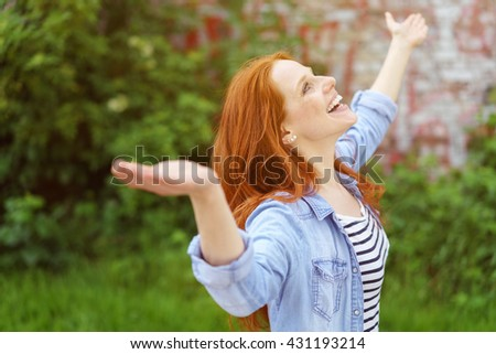 Happy young woman celebrating the spring standing outdoors in a lush green garden with outspread arms and a beaming smile - stock photo