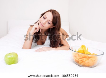 happy young woman choosing between an apple and potato chips in bed at home - stock photo