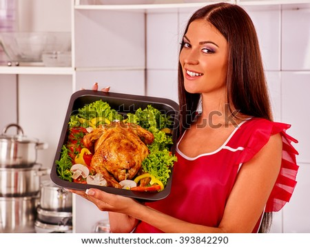 Happy young woman cooking chicken at home kitchen.  Poultry preparation.