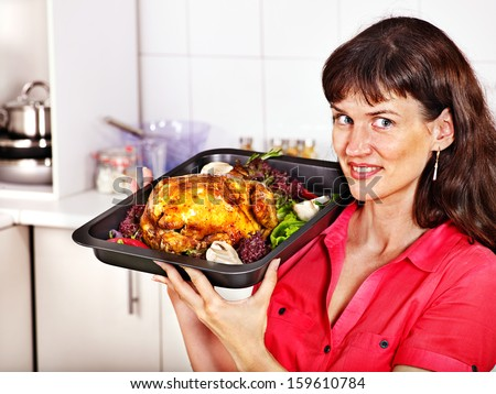 Happy young woman cooking chicken at kitchen.