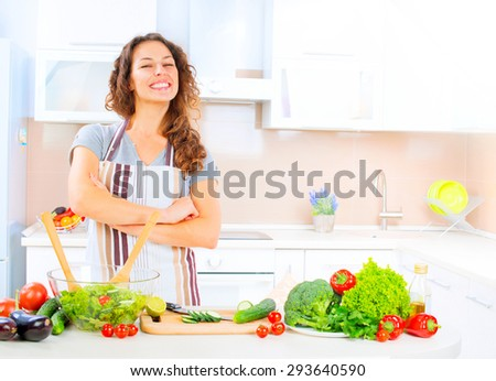Happy Young Woman Cooking in the kitchen at home Healthy Food, Vegetable Salad. Diet. Dieting Concept. Healthy Lifestyle. Prepare Food. Slimming, weight loss - stock photo