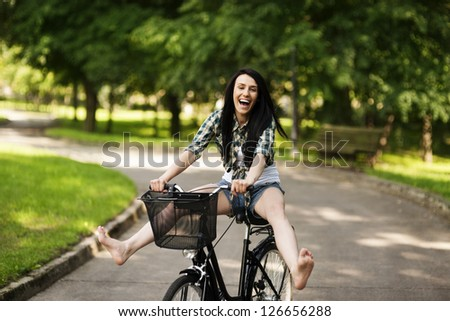 Happy young woman cycling through the park - stock photo