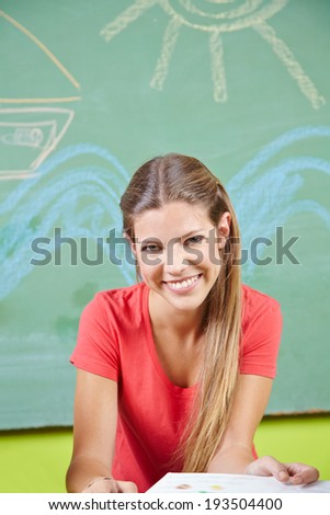 Happy young woman doing education as child care worker in a kindergarten - stock photo