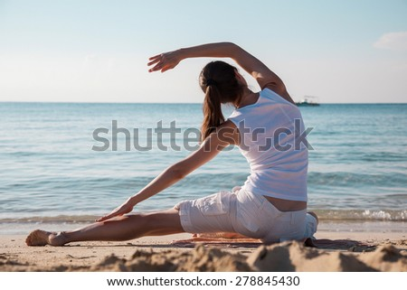Happy young woman doing exercises on a sea coast at dawn - stock photo