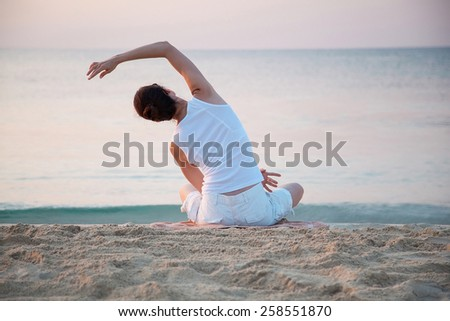 Happy young woman doing exercises sitting on sea coast at dawn - stock photo