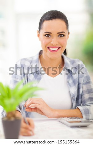 happy young woman doing her finances at home - stock photo