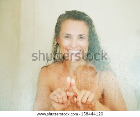 Happy young woman drawing heart in weeping glass shower door - stock photo
