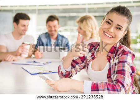 Happy young woman dressed casual sitting at office with colleagues on background.