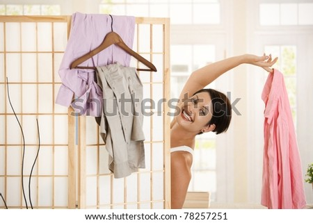 Happy young woman dressing up, looking out behind dressing panel, showing up pink shirt. - stock photo