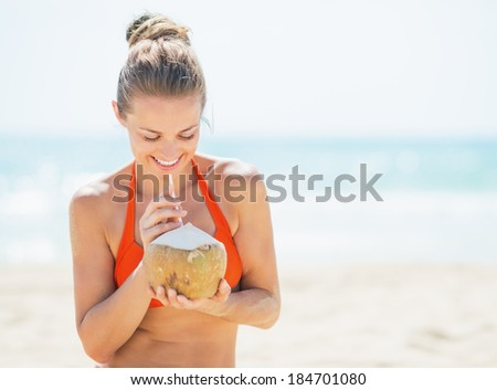 Happy young woman drinking coconut milk on beach - stock photo