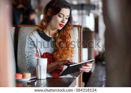 Happy young woman drinking coffee / tea and using tablet computer in a coffee shop. Attractive young woman with tablet in cafe. Smiling girl spending time in a street cafe using digital tablet - stock photo