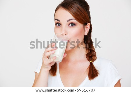 happy young woman drinking milk over grey background - stock photo
