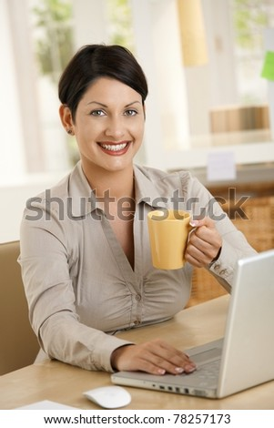 Happy young woman drinking tea at desk, using laptop computer, smiling.