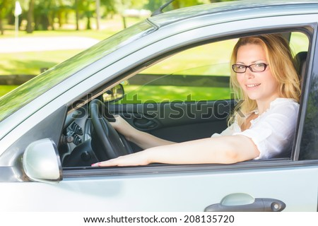 Happy young woman driving a car. - stock photo