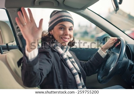 Happy young woman driving a car and waving - stock photo