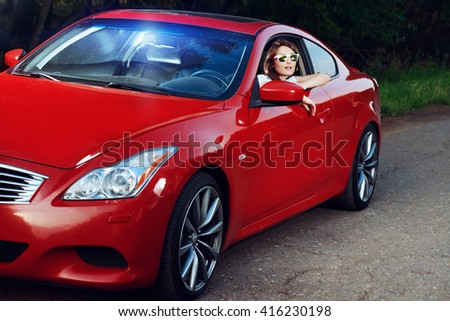 Happy young woman driving her red sports car. Traveling concept.  - stock photo