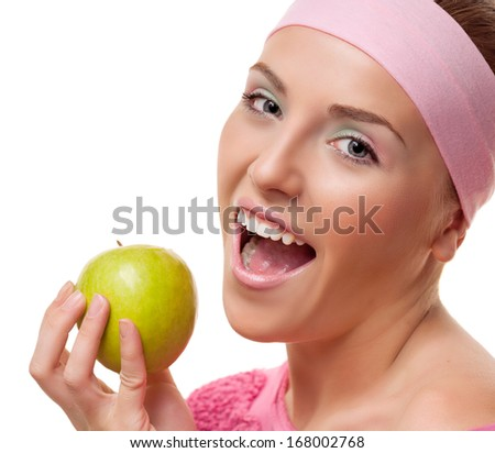 happy young woman eating a green apple, isolated against white background - stock photo