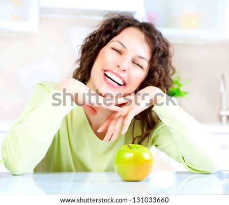 Happy Young Woman Eating Apple on Kitchen. Diet. Dieting concept. Healthy food. Loosing Weight