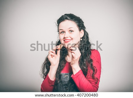 Happy young woman eating cookies, dressed in a overalls, close-up isolated on a gray background - stock photo