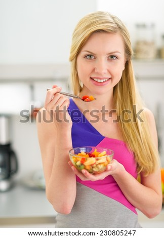 Happy young woman eating fruits salad in kitchen