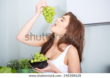Happy young woman eating grapes in a kitchen - stock photo