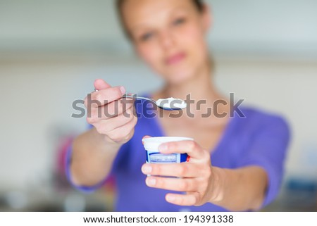 Happy young woman eating yogurt in kitchen - stock photo