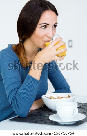 Happy Young Woman Enjoying Breakfast in the kitchen at the morning - stock photo