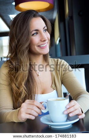 Happy young Woman Enjoying Drink In Cafe