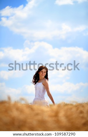 Happy young woman enjoying in sun on the wheat field