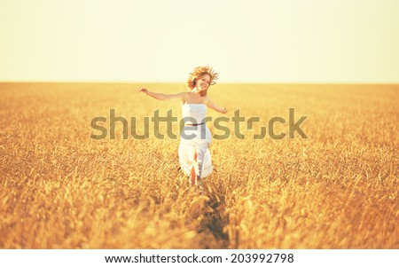 happy young woman enjoying life in golden wheat field - stock photo