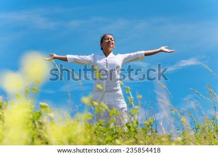 Happy young woman enjoying sunny day. - stock photo